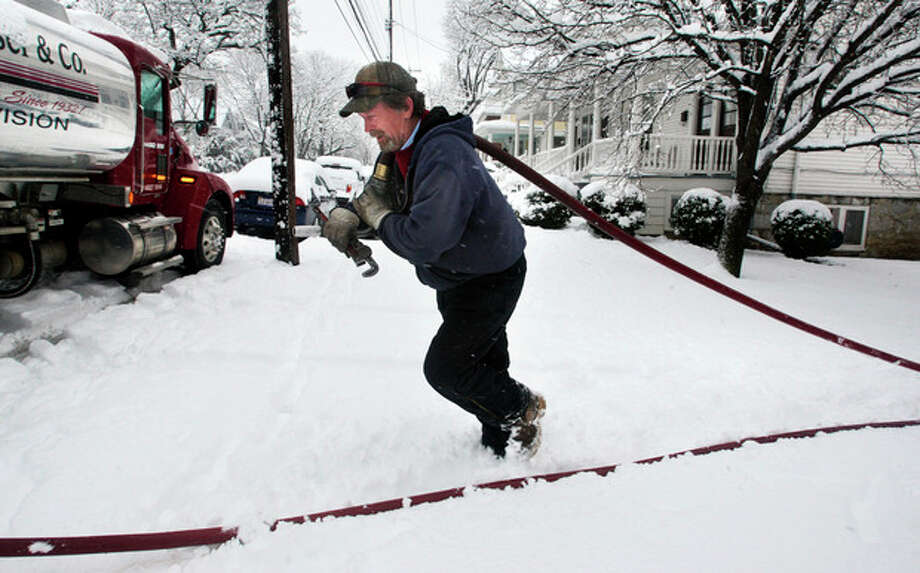 FILE - In this Wednesday, March 6, 2013, file photo, delivery truck driver Donald Whitacre, of Gore, Va., returns to his truck after pumping 200-gallons of home heating oil into a customer's tank during heavy snowfall in Winchester, Va. Chillier weather and slightly higher fuel prices may make the winter of 2013-14, the most expensive one in three years for U.S. residents. (AP Photo/The Winchester Star, Jeff Taylor, File) / The Winchester Star