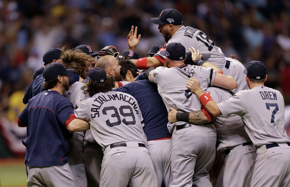 The Boston Red Sox's celebrate on the field after defeating the Tampa Bay Rays in Game 4 of an American League baseball division series, Wednesday, Oct. 9, 2013, in St. Petersburg, Fla. The Boston Red Sox's defeated the Tampa Bay Rays 3-1 to move on to the American League Championship Series. (AP Photo/Chris O'Meara)