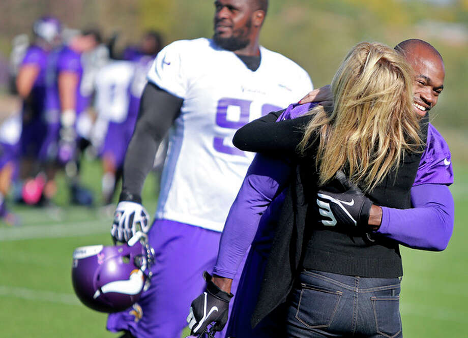 Minnesota Vikings' Adrian Peterson, right, receives a hug from an unidentified person during an NFL football practice field at Winter Park in Eden Prairie, Minn., Friday, Oct. 11, 2013. Peterson said he is certain he will play Sunday despite a serious personal matter that caused him to miss practice earlier this week. (AP Photo/The Star Tribune, Elizabeth Flores) ST. PAUL PIONEER PRESS OUT; SOFT OUT MINNEAPOLIS-AREA TV NOT TV OUT; MAGAZINES OUT / The Star Tribune