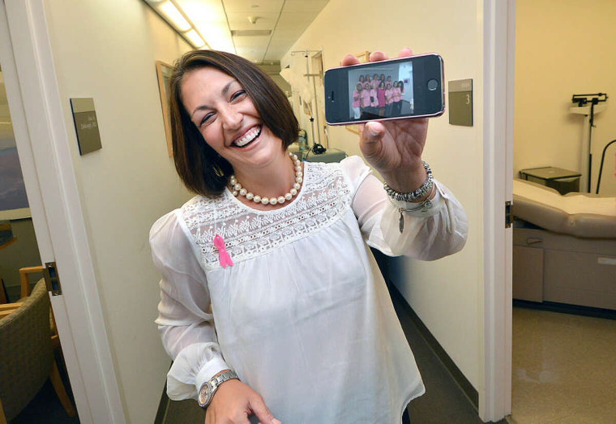 Stamford Hospital's Dr. Elaine Morganelli shows a photo of her staff in pink for Breast Cancer Awareness Month.