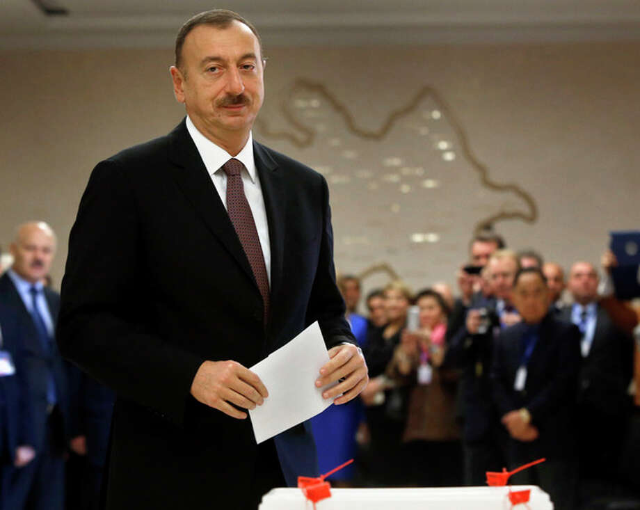 Azerbaijan President Ilham Aliyev prepares to cast his ballot paper during the voting at a polling station in Baku, Azerbaijan, Wednesday, Oct. 9, 2013. Oil-rich Azerbaijan is booming and the wealth is trickling down to its poorest people. It all means that its president doesn't even need to clamp down too hard to ensure he extends a decades-long dynastic rule in elections on Wednesday. (AP Photo/Sergei Grits) / AP