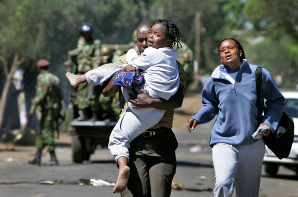 FILE - In this Thursday, Jan. 3, 2008 file photo, a young girl cries as she is carried by a man and woman fleeing an area of wooden kiosks which was set on fire by supporters of Raila Odinga's party, the Orange Democratic Movement (ODM), during post-election violence in the Kibera slum area of Nairobi, Kenya. Kenya's foreign minister Amina Mohamed said at a news conference Wednesday, Oct. 9, 2013 that no sitting president in the world has had to appear before a court, a statement that comes as Kenya appears to be laying the groundwork to avoid having President Uhuru Kenyatta appear at the International Criminal Court next month. (AP Photo/Ben Curtis, File)