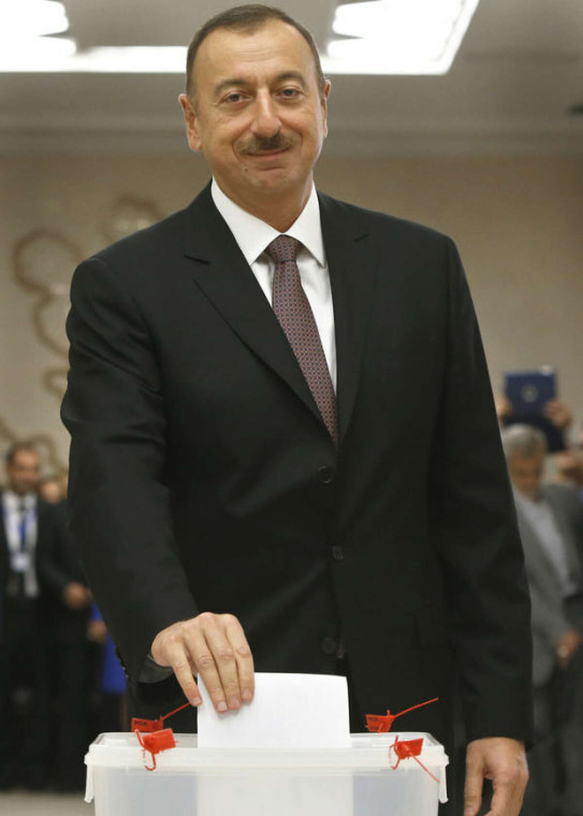 Azerbaijan President Ilham Aliyev casts his ballot paper during the voting at a polling station in Baku, Azerbaijan, Wednesday, Oct. 9, 2013. Presidential election begins in the oil-rich Caspian nation. (AP Photo/Sergei Grits)