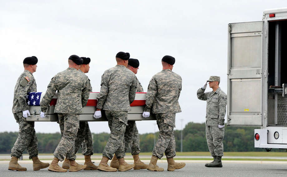 An Army carry team moves a transfer case containing the remains of Pfc. Cody J. Patterson Wednesday, Oct. 9, 2013 at Dover Air Force Base, Del. According to the Department of Defense, Patterson, 24, of Philomath, Ore., died Oct. 6, 2013 in Zhari district, Afghanistan of injuries sustained when enemy forces attacked his unit with an improvised explosive device. (AP Photo/Steve Ruark) / FR96543 AP