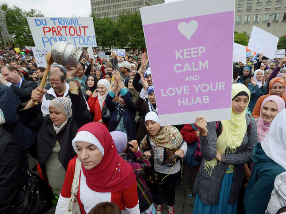 """Demonstrators take part in a protest against Quebec's proposed """"charter of values"""" in Montreal on Saturday Sept. 14, 2013. The plan by the ruling party, the separatist Parti Quebecois, to make the provincial government religion-neutral, is trying to ban some symbols of religious faith such as Jewish skullcaps, Sikh turbans, Muslim head scarves and large crucifixes from public work places. (AP Photo/The Canadian Press, Ryan Remiorz) / The Canadian Press"""