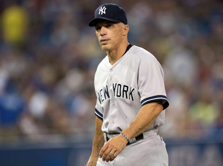 FILE - In this Aug. 28, 2013, file photo, New York Yankees manager Joe Girardi walks off the field during a baseball game against the Toronto Blue Jays in Toronto. Girardi signed a four-year contract extension to stay with the New York Yankees, Wednesday, Oct. 9, 2013. (AP Photo/The Canadian Press, Frank Gunn, File) / The Canadian Press