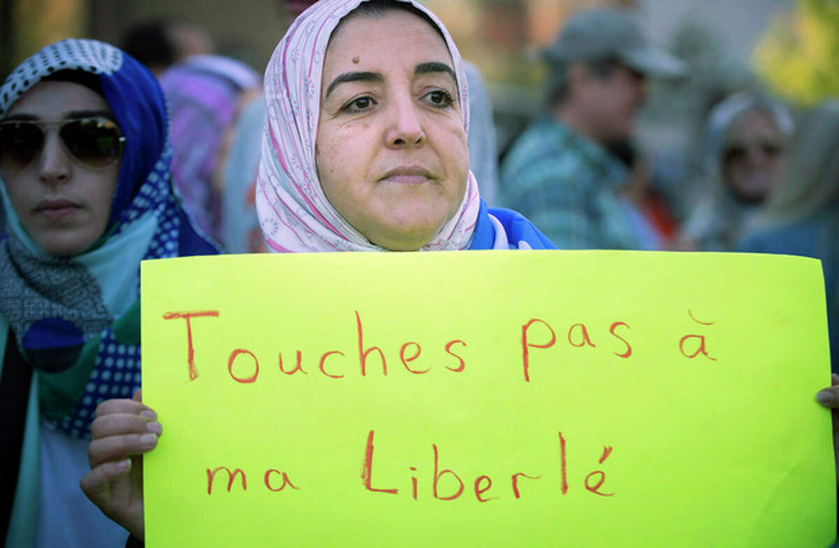 """A protester holds a sign which reads in French, """"Do not touch my Freedom"""" during a protest in Montreal on Sunday, Sept. 29, 2013 against the """"charter of values"""" proposed by the ruling Parti Quebecois. (AP Photo/The Canadian Press, Peter McCabe)"""
