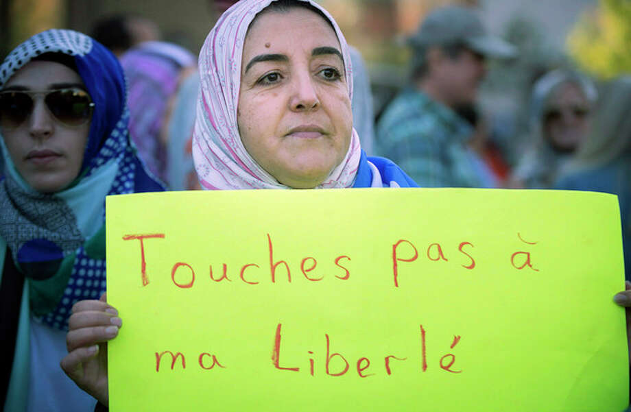 "A protester holds a sign which reads in French, ""Do not touch my Freedom"" during a protest in Montreal on Sunday, Sept. 29, 2013 against the ""charter of values"" proposed by the ruling Parti Quebecois. (AP Photo/The Canadian Press, Peter McCabe) / The Canadian Press"
