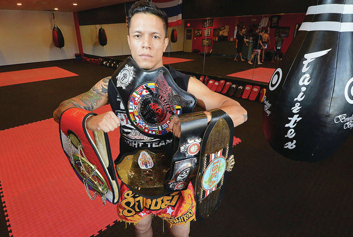 Hour photo/Alex von Kleydorff Eddie Martinez holds some of the championship belts he has earned in for Muy Thai kickboxing in his Sitan Gym in Norwalk. Martinez won the New York state championship last month.