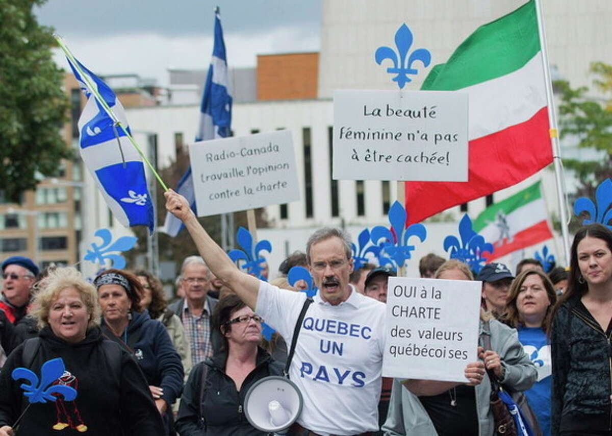 """Supporters of a proposed Quebec """"charter of values"""" march in Montreal, Sunday, Sept. 22, 2013. The proposed charter would ban the wearing of some religious symbols and clothing from public institutions if brought into law. (AP Photo/The Canadian Press, Graham Hughes)"""