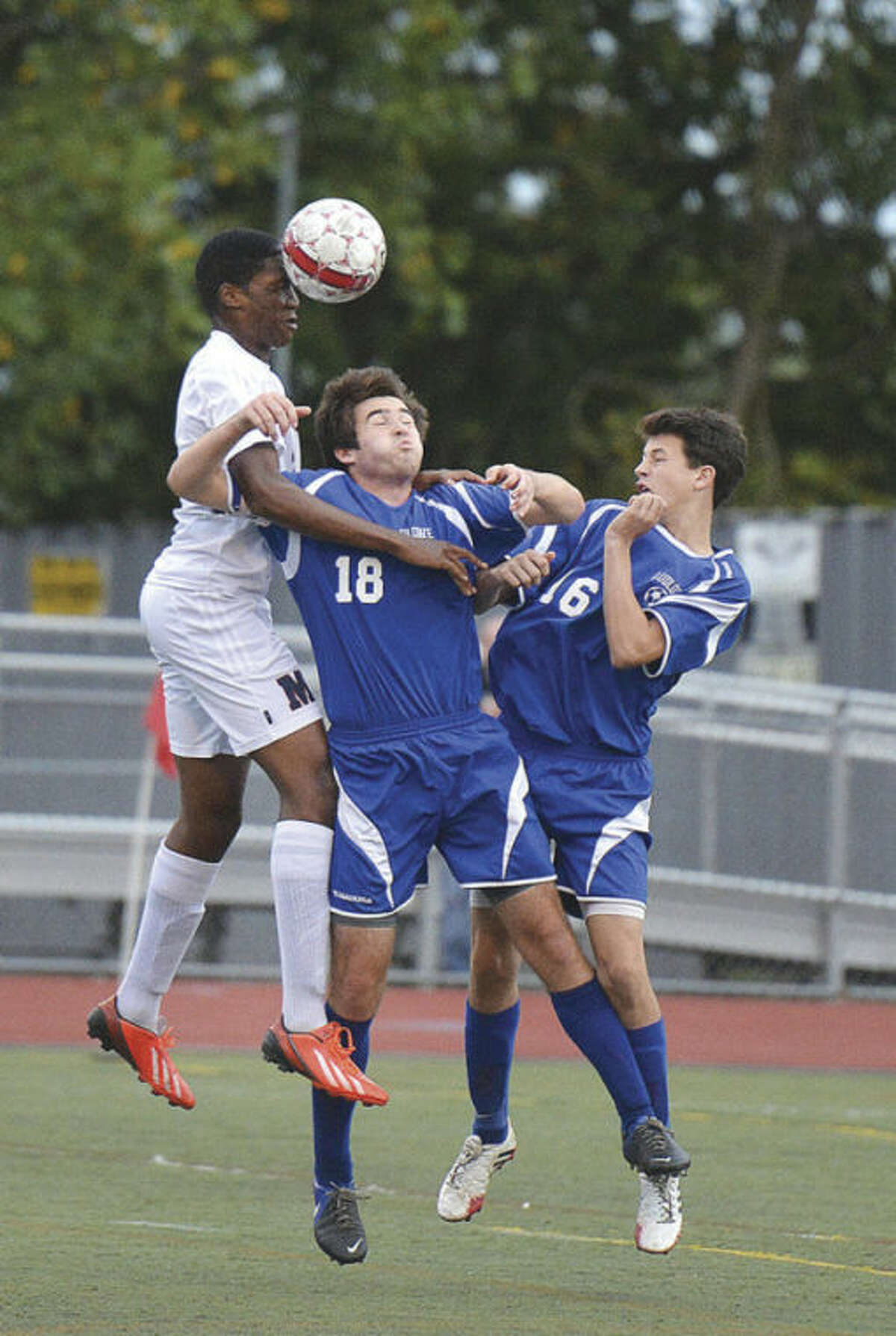 Hour photo/Alex von Kleydorff Brien McMahon's Jonathan Weeks, left, outleaps Ludlowe's Jordan Layne (18) and Brendan Layne (16) to head the ball during Wednesday's contest at BMHS. The Senators posted a 1-0 victory over the visiting Falcons.