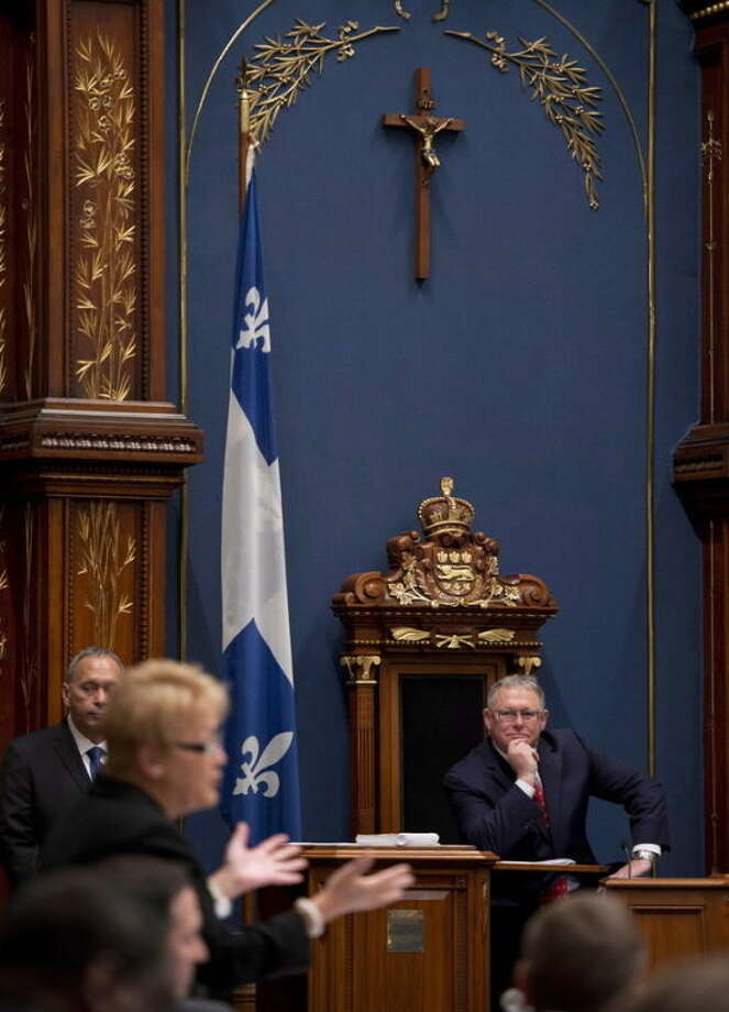 """A crucifix hangs in the legislature in Quebec City as Quebec Premier Pauline Marois responds to opposition questions on Wednesday, Sept. 18, 2013. Michel Lincourt, who heads an association of Quebec secularists, defends the """"charter of values"""" proposal and wants it to go further by removing the crucifix from the legislature. (AP Photo/The Canadian Press, Jacques Boissinot)"""