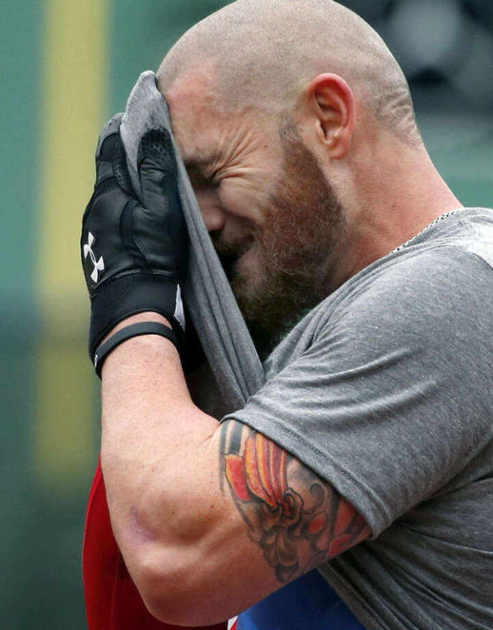 Boston Red Sox's Jonny Gomes wipes his face during a baseball workout at Fenway Park in Boston, Thursday, Oct. 10, 2013 in preparation for Game 1 of the American League championship series on Saturday. (AP Photo/Elise Amendola)