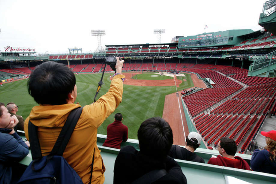 Fans on a tour of Fenway Park in Boston watch from the Green Monster seats as Boston Red Sox baseball players work out on Thursday, Oct. 10, 2013 in preparation for Game 1 of the AL championship series on Saturday. (AP Photo/Elise Amendola) / AP