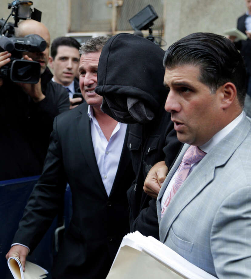 Wojciech Braszczok, center, with face covered, leaves the courthouse in New York, Wednesday, Oct. 9, 2013. Braszczok, an undercover police detective, was charged with gang assault in a motorcycle rally that descended into violence in New York. (AP Photo/Seth Wenig) / AP