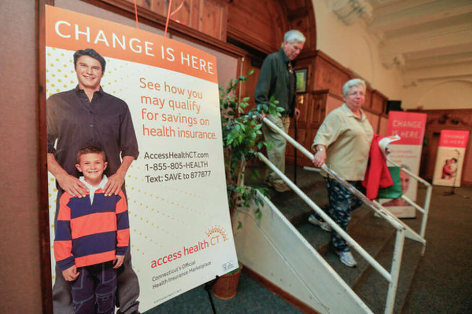 Hour photo/ Chris PalermoLynne and Richard Emmons enter the room for the overview of the healthcare reform put on by Access Health CT at City Hall on Thursday night. / © 2013 Hour Newspapers All Rights Reserved