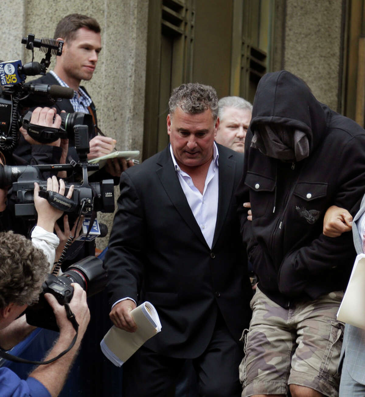 Wojciech Braszczok, right, with face covered, leaves the courthouse in New York, Wednesday, Oct. 9, 2013. Braszczok, an undercover police detective, was charged with gang assault in a motorcycle rally that descended into violence in New York. (AP Photo/Seth Wenig)