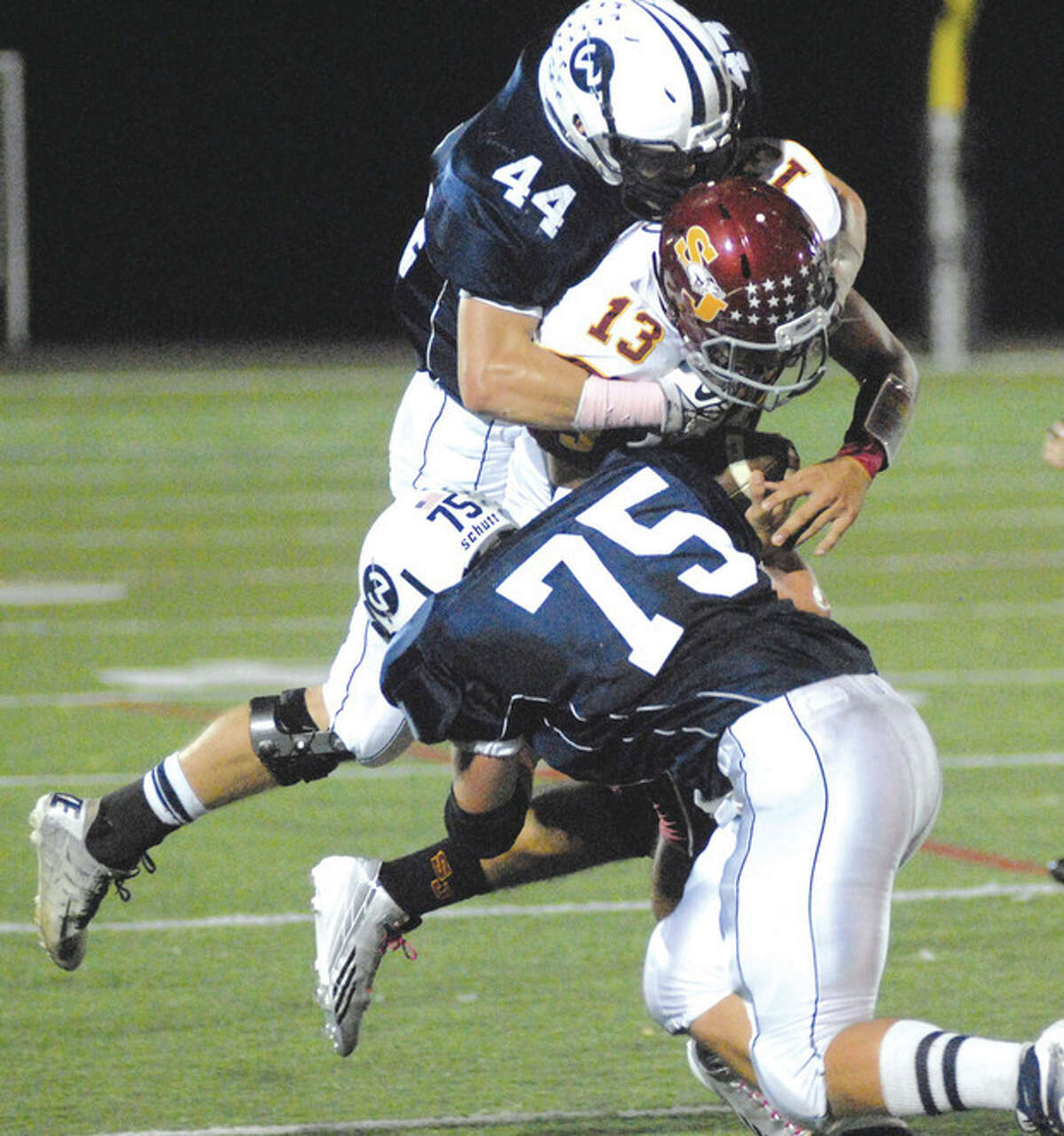 Hour photo/John Nash Wilton's Jack Dexter (44) and Tyler Mirable (75) make a Cadet sandwich out of St. Joseph quarterback Jordan Vazzano during Friday night's FCIAC football game at Fujitani Field in Wilton. Vazzano got the last laugh leading the Cadets to a 44-20 victory.