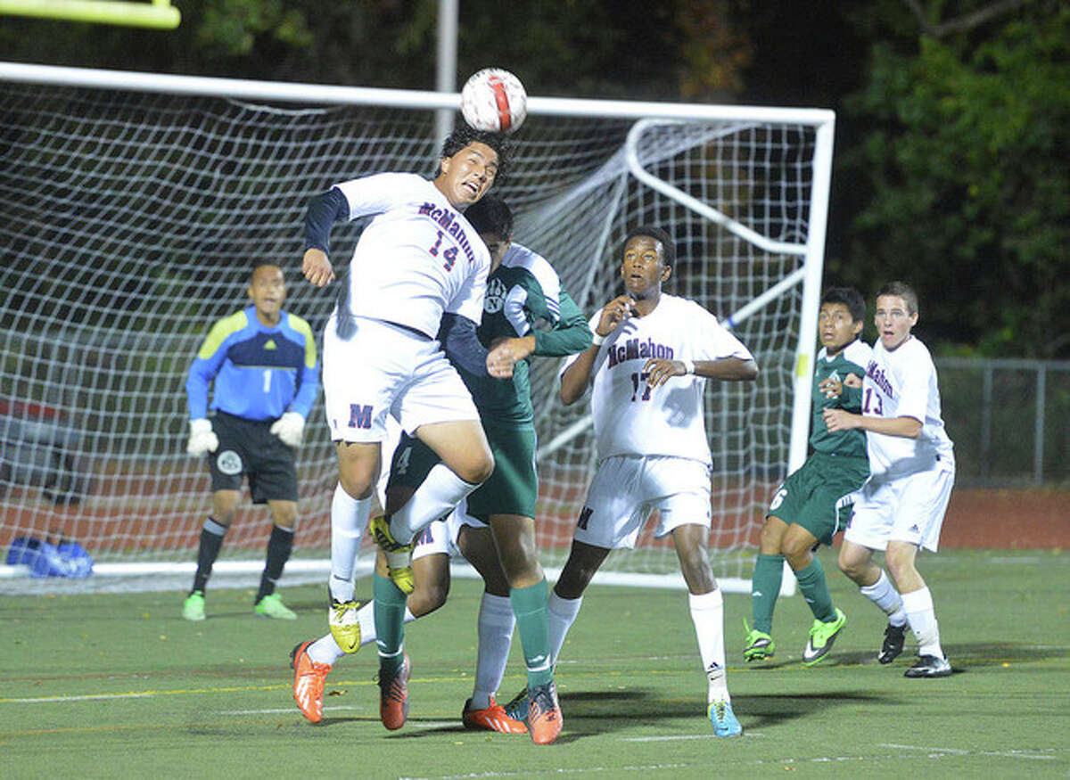 Hour photo/Alex von Kleydorff Brien McMahon's Sergio Ceja (14) heads the ball away from the goal and Norwalk's Loizos Karaiskos during some close action in front of the Senators' goal during Friday night's game at Casagrande Field. Michael Jean-Charles (17) of the Senators gets a close-up look at the play. Norwalk won the crosstown clash, 1-0.