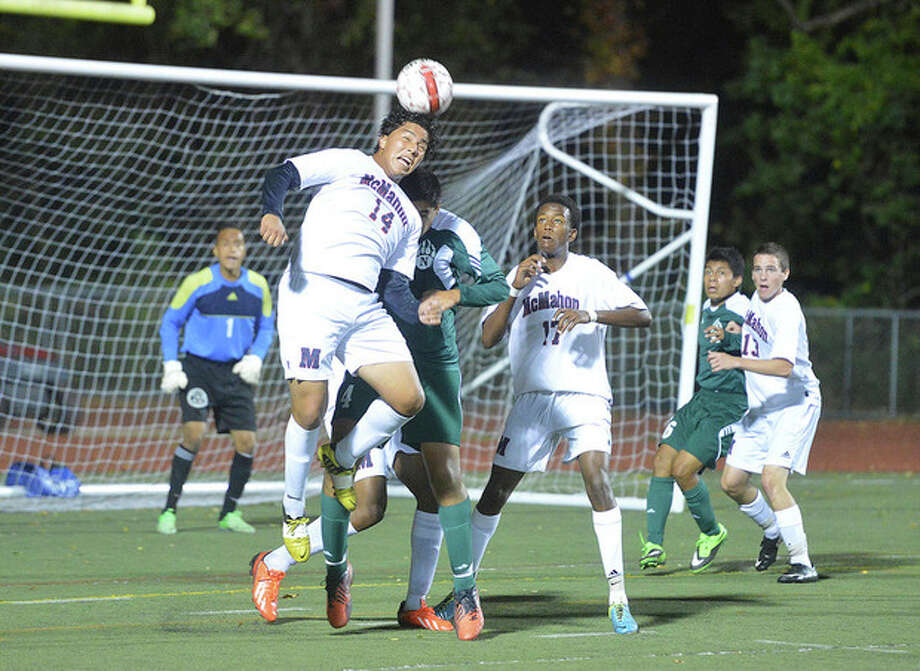 Hour photo/Alex von KleydorffBrien McMahon's Sergio Ceja (14) heads the ball away from the goal and Norwalk's Loizos Karaiskos during some close action in front of the Senators' goal during Friday night's game at Casagrande Field. Michael Jean-Charles (17) of the Senators gets a close-up look at the play. Norwalk won the crosstown clash, 1-0.