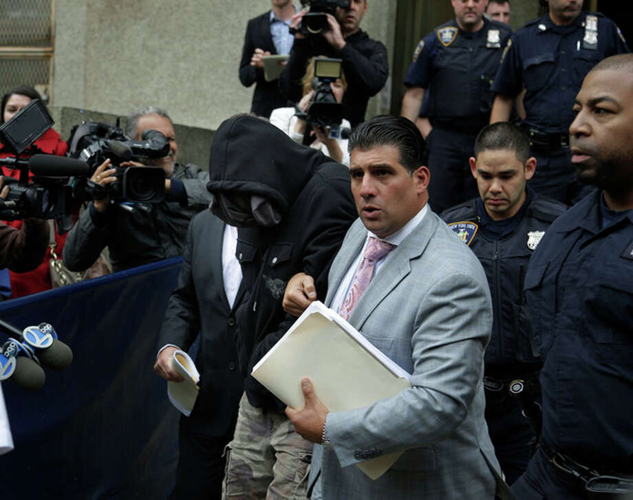 Wojciech Braszczok, center left, with face covered, leaves the courthouse in New York, Wednesday, Oct. 9, 2013. Braszczok, an undercover police detective, was charged with gang assault in a motorcycle rally that descended into violence in New York. (AP Photo/Seth Wenig) / AP