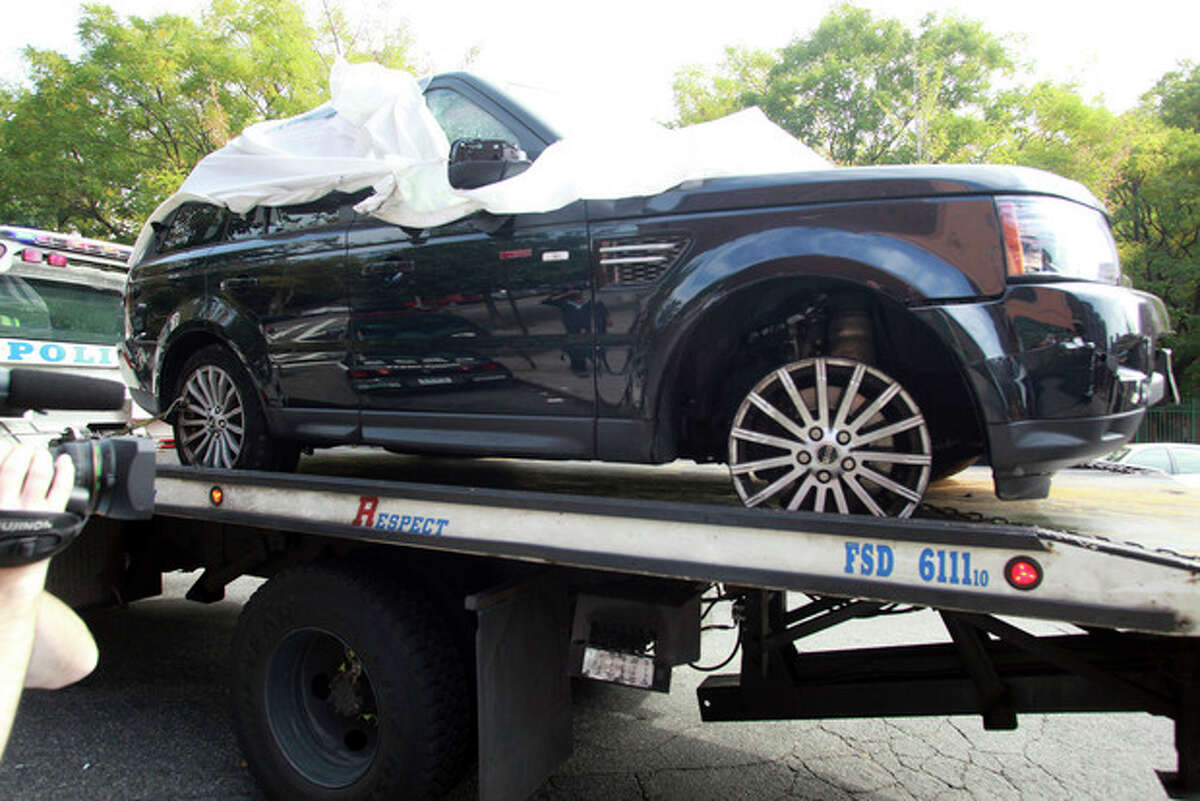 FILE - In this Oct. 5, 2013 file photo,The Range Rover involved in the bikers attack is moved from the police precinct for further police investigation in New York. An off-duty New York Police Department undercover detective apparently seen on video pounding on an SUV during a melee with motorcyclists has been arrested, Tuesday, Oct. 8, 2013. (AP Photo/David Karp, File)