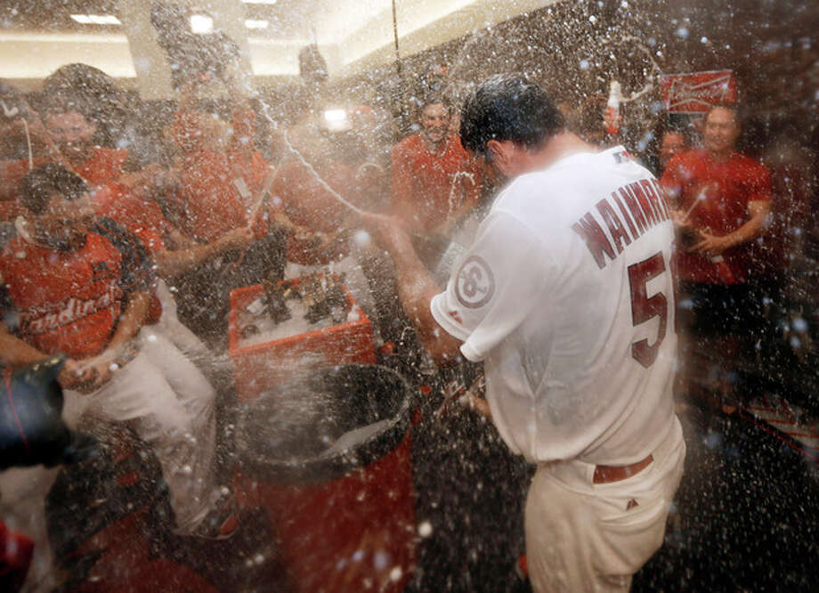 St. Louis Cardinals pitcher Adam Wainwright (50) celebrates in the locker room after the Cardinals defeated the Pittsburgh Pirates 6-1 in Game 5 in a National League baseball division series, Wednesday, Oct. 9, 2013, in St. Louis. The Cardinals advanced to the NL championship series against the Los Angeles Dodgers. (AP Photo/Jeff Roberson) / AP