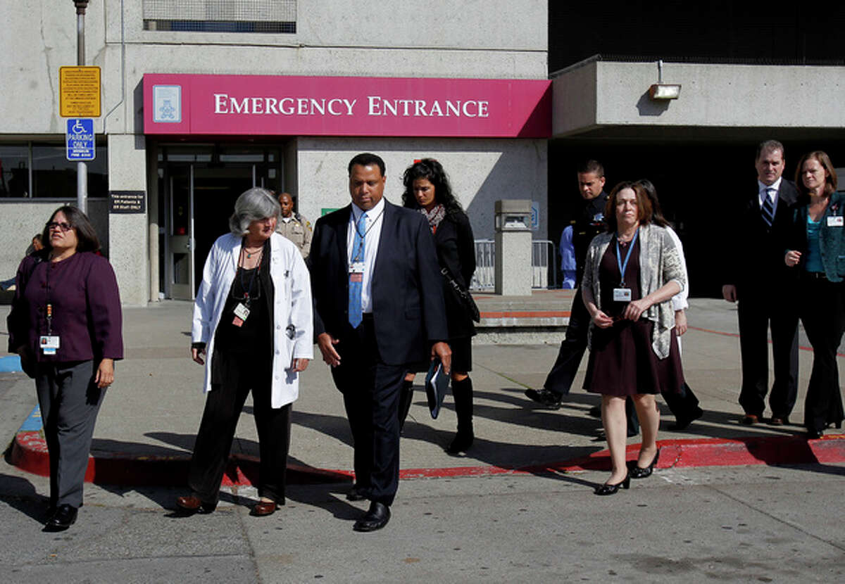 San Francisco General Hospital staff walk to a media conference at the hospital Tuesday, Oct. 9, 2013 in San Francisco. Officials confirmed the identity of a woman's body that had been discovered in a rarely used stairwell at the hospital more than two weeks ago as that of Lynne Spalding, 57, a native of England. Spalding was being treated for an infection at the hospital when she disappeared from her room on Sept. 21, 2013. (AP Photo/San Francisco Chronicle, Brant Ward)