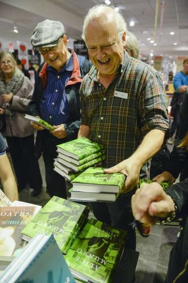 The books of 2013 Nobel literature prizewinner, Canadian Alice Munro, are snatched from the shelves of a Stockholm bookstore, minutes after the prize announcement from the Royal academy, Thursday Oct. 10, 2013. (AP Photo/Jessica Gow) ** SWEDEN OUT **