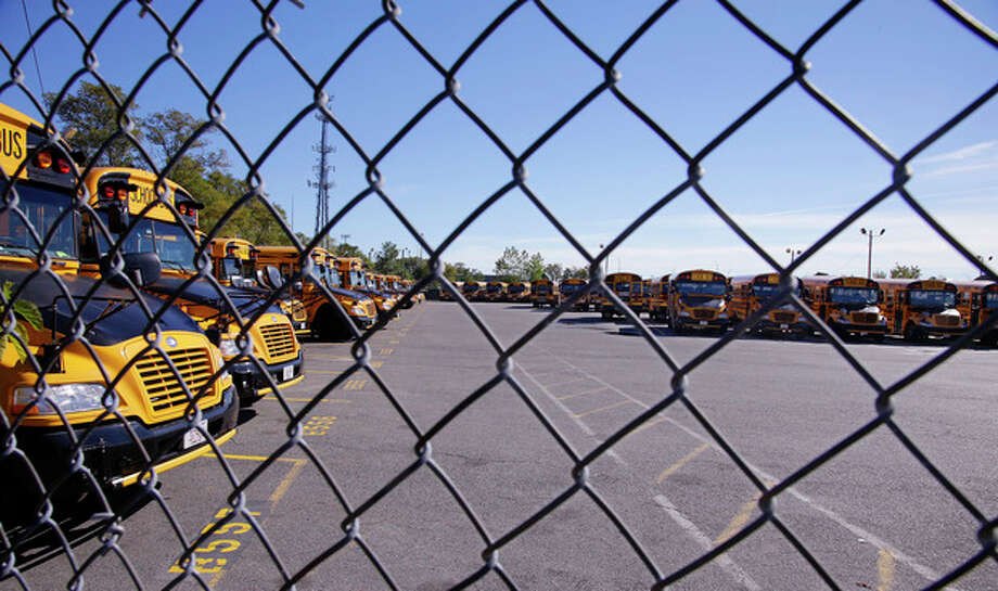 Boston school busses sit idle behind a chain link fence at Veolia Transportation, the city's school bus contractor, in Boston, Tuesday, Oct. 8, 2013. About 600 school bus drivers have gone on strike affecting most of the school district's 33,000 students. (AP Photo/Stephan Savoia) / AP2013