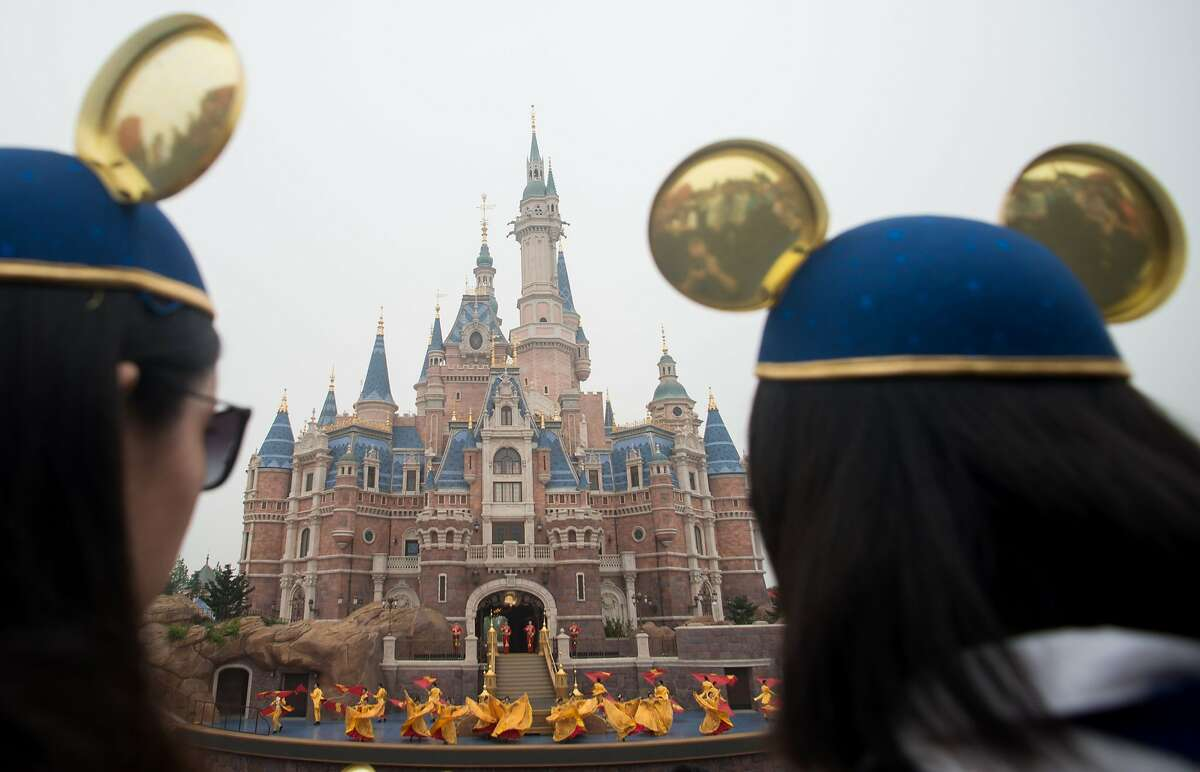 Women wearing Mickey Mouse ears watch the opening ceremony of the Shanghai Disney Resort in Shanghai on June 16, 2016. Entertainment giant Disney brings the ultimate American cultural concept to Communist-ruled China on June 16, opening a massive theme park in Shanghai catering to a rising middle class. / AFP PHOTO / JOHANNES EISELEJOHANNES EISELE/AFP/Getty Images