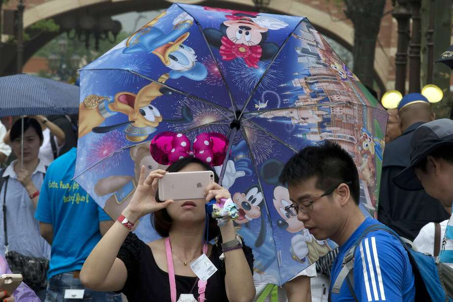 A woman takes photo on her phone during the opening day of the Disney Resort in Shanghai, China, Thursday, June 16, 2016. Walt Disney Co. opened its first theme park in mainland China on Thursday at a ceremony that mixed speeches by Communist Party officials, a Chinese children's choir and actors dressed as Sleeping Beauty and other Disney characters. (AP Photo/Ng Han Guan) Photo: Ng Han Guan, Associated Press