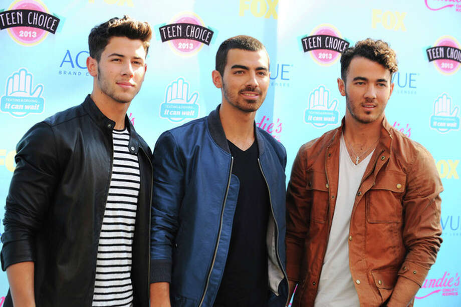 FILE - In this Aug. 11, 2013 file photo, from left, Nick Jonas, Joe Jonas and Kevin Jonas of the musical group Jonas Brothers arrive at the Teen Choice Awards at the Gibson Amphitheater, in Los Angeles. The Jonas Brothers are canceling their tour two days before it begins on Oct. 11, 2013. (Photo by Jordan Strauss/Invision/AP, File) / Invision