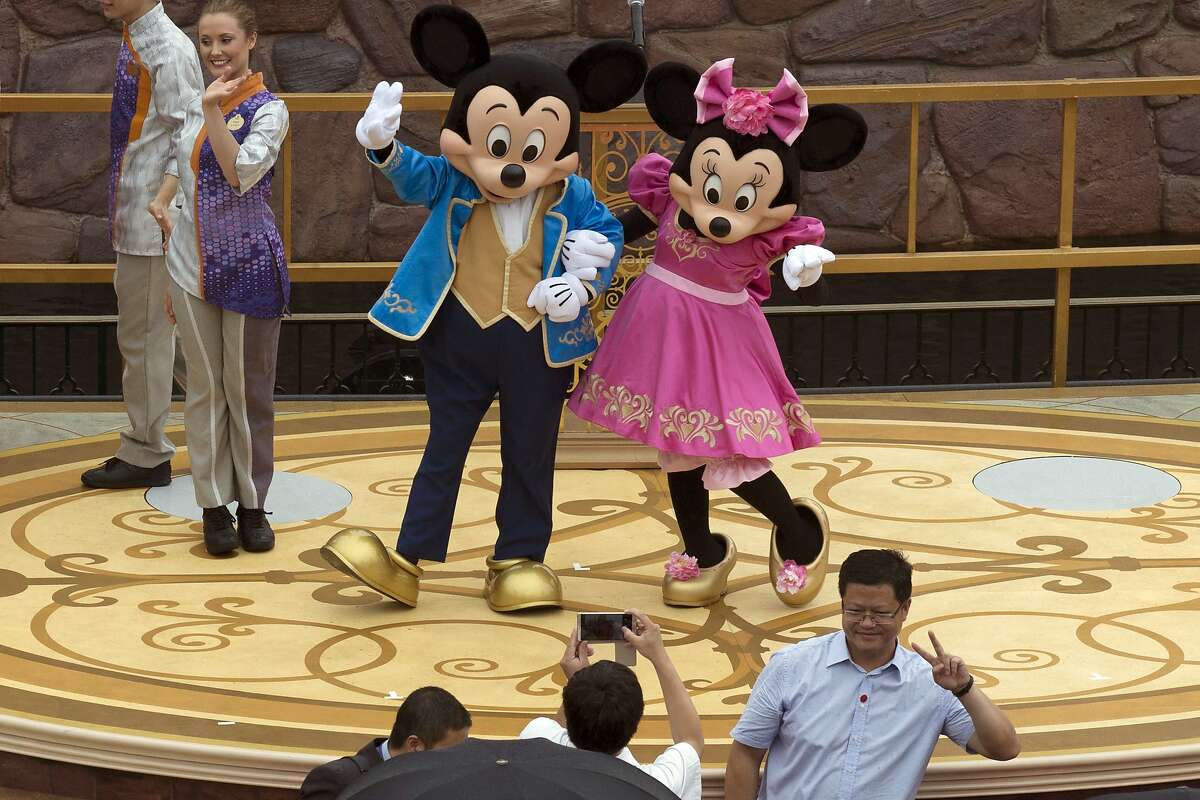 Mickey and Minnie Mouse pose for a photograph at the opening ceremony for the Disney Resort in Shanghai, China, Thursday, June 16, 2016. Walt Disney Co. opened its first theme park in mainland China on Thursday at a ceremony that mixed speeches by Communist Party officials, a Chinese children's choir and actors dressed as Sleeping Beauty and other Disney characters. (AP Photo/Ng Han Guan)