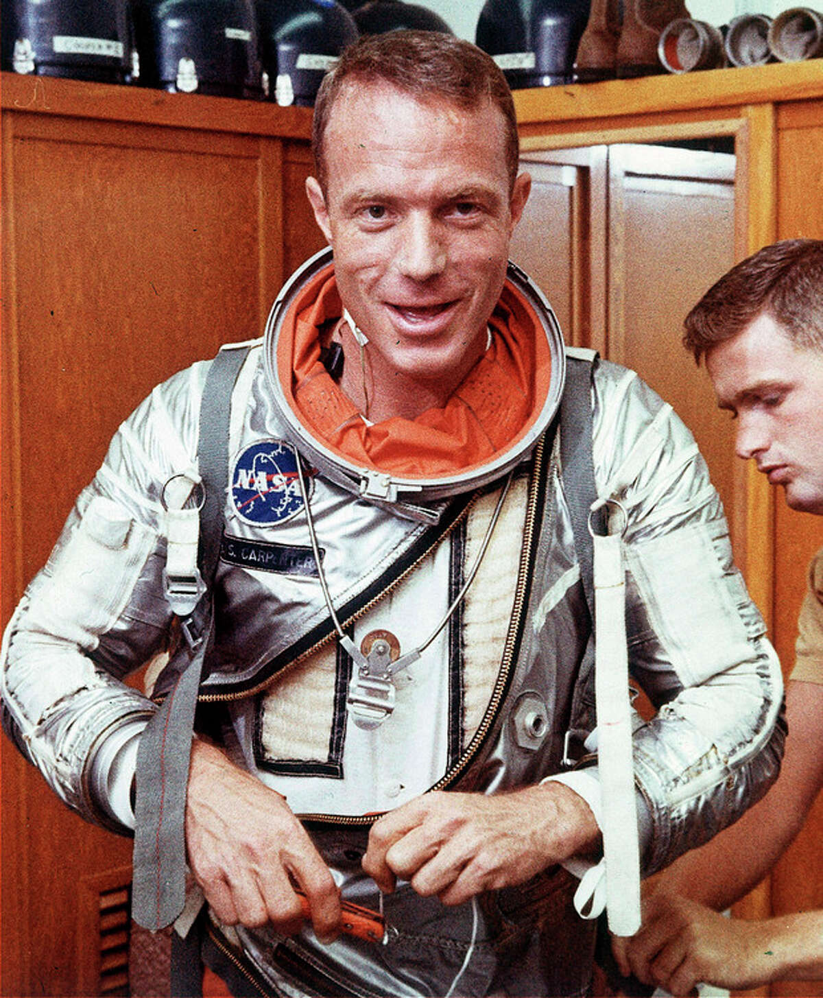 FILE - In this Aug. 1962 file photo, astronaut Scott Carpenter has his space suit adjusted by a technician in Cape Canaveral, Fla. Carpenter, the second American to orbit the Earth and one of the last surviving original Mercury 7 astronauts, died Thursday, Oct. 10, 2013. He was 88. (AP Photo, File)