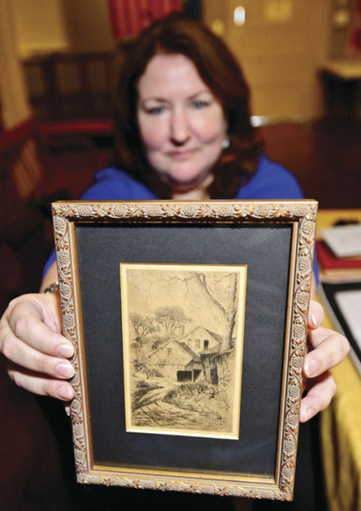 Hour photo / Erik Trautmann Suzanne Betts holds an etching of the old Betts Mill, built in 1709 and was destroyed by fire in 1921. Betts is descended from several of Norwalk's founding families and is currently president of the Norwalk Historical Society.