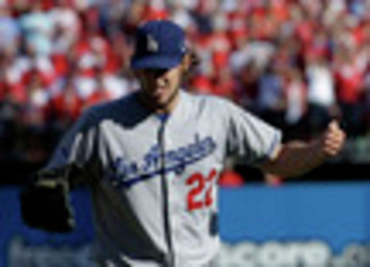 Los Angeles Dodgers starting pitcher Clayton Kershaw punches the air after getting St. Louis Cardinals' Yadier Molina to fly out during the first inning of Game 2 of the National League baseball championship series Saturday, Oct. 12, 2013, in St. Louis. (AP Photo/David J. Phillip)