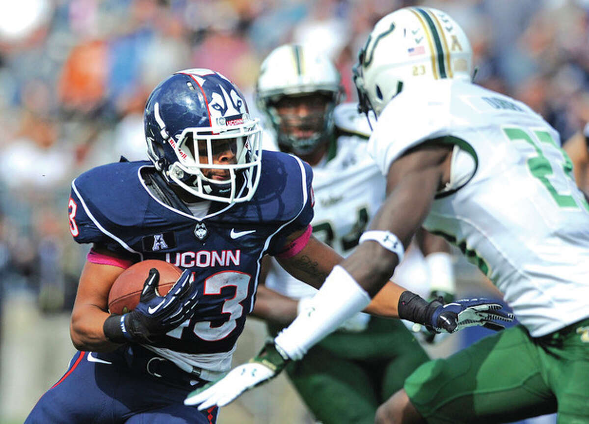 AP photo UConn running back Lyle McCombs, left, tries to get around South Florida defensive back Kenneth Durden during a 52-yard touchdown run. McCombs ran for a career-high 164 yards but the winless Huskies dropped a 13-10 decision to the Bulls.