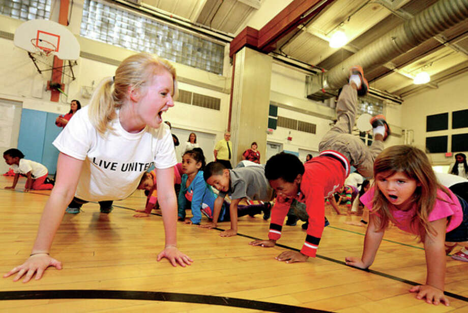Hour photos / Erik TrautmannVolunteers like Cynthia Beckwith (bottom) teach kindergartners, including Samantha Wherle and Jasmin Lopez (top), yoga at Brookside Elementary School yoga as the student body learns about fitness and health through The United Way Day of Caring program Friday. / (C)2013, The Hour Newspapers, all rights reserved