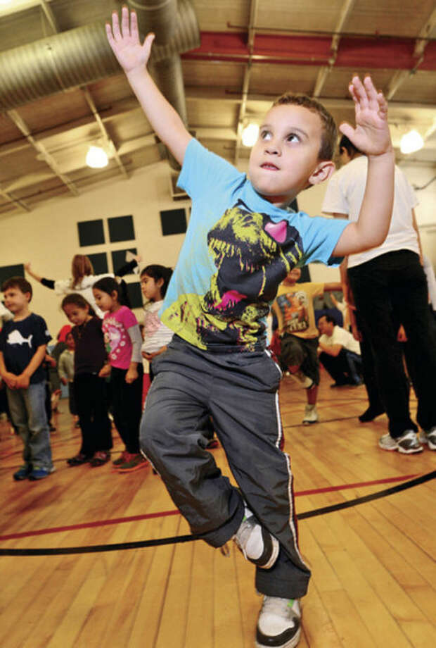Hour photo / Erik Trautmann Volunteers teach kindergartners at Brookside Elementary School including Juan Garcia yoga as the student body learns about fitness and health through The United Way Day of Caring program Friday.