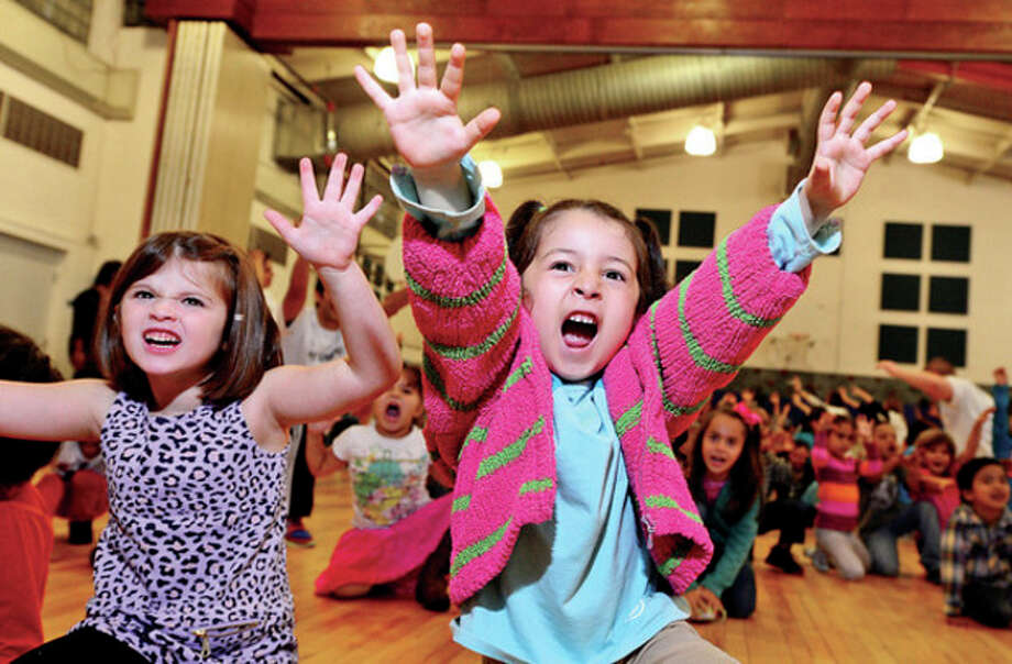 Hour photo / Erik TrautmannVolunteers teach kindergartners at Brookside Elementary School including Samantha Wherle and Jasmin Lopez yoga as the student body learns about fitness and health through The United Way Day of Caring program Friday. / (C)2013, The Hour Newspapers, all rights reserved