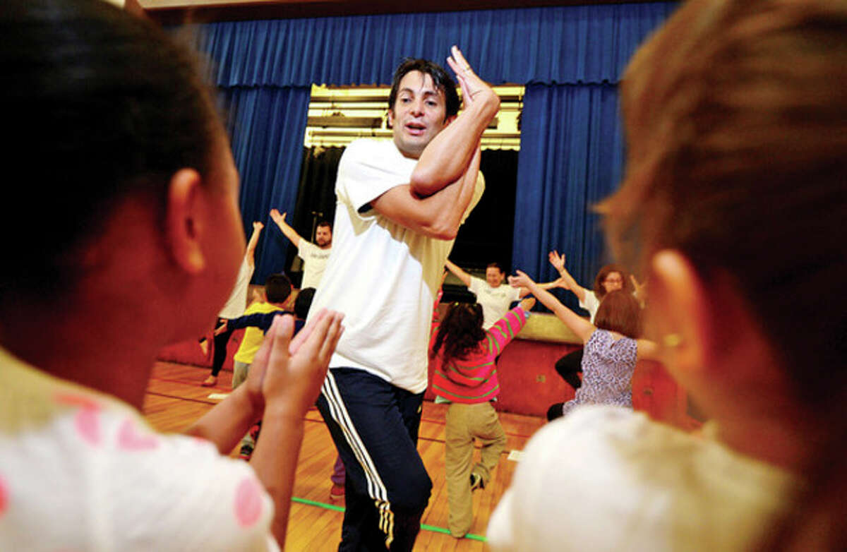 Hour photo / Erik Trautmann Volunteer Jose Lleras teaches kindergartners at Brookside Elementary School yoga as the student body learns about fitness and health through The United Way Day of Caring program Friday. See page A5 for more photos.