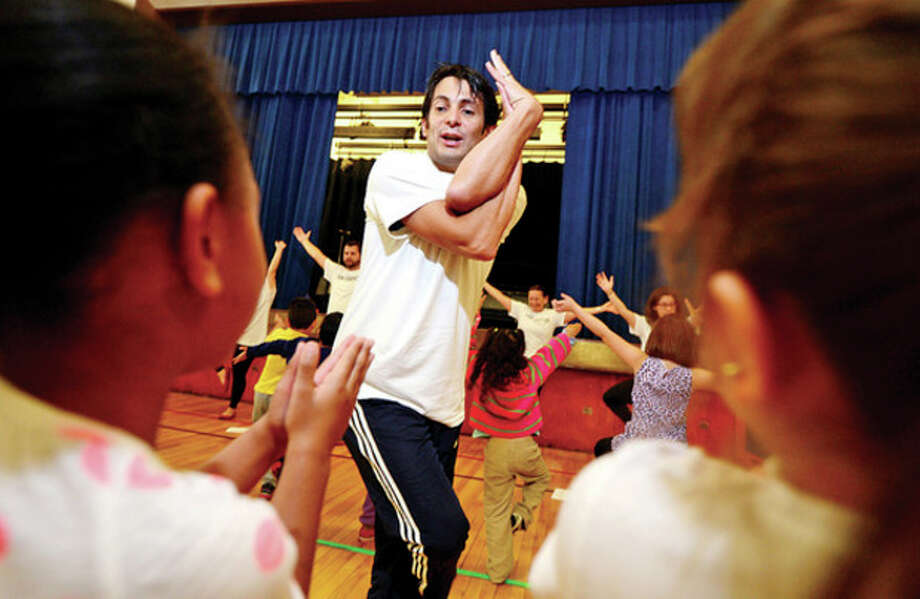 Hour photo / Erik TrautmannVolunteer Jose Lleras teaches kindergartners at Brookside Elementary School yoga as the student body learns about fitness and health through The United Way Day of Caring program Friday. See page A5 for more photos. / (C)2013, The Hour Newspapers, all rights reserved