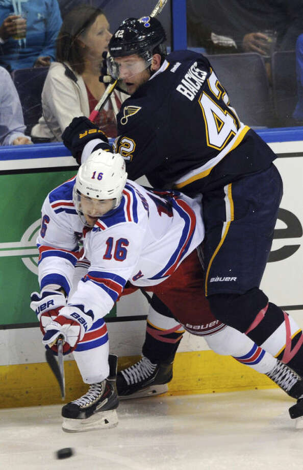 St. Louis Blues' David Backes (42) battles with New York Rangers' Derick Brassard (16) during the second period of an NHL hockey game on Saturday, Oct. 12, 2013, in St. Louis. (AP Photo/Bill Boyce)