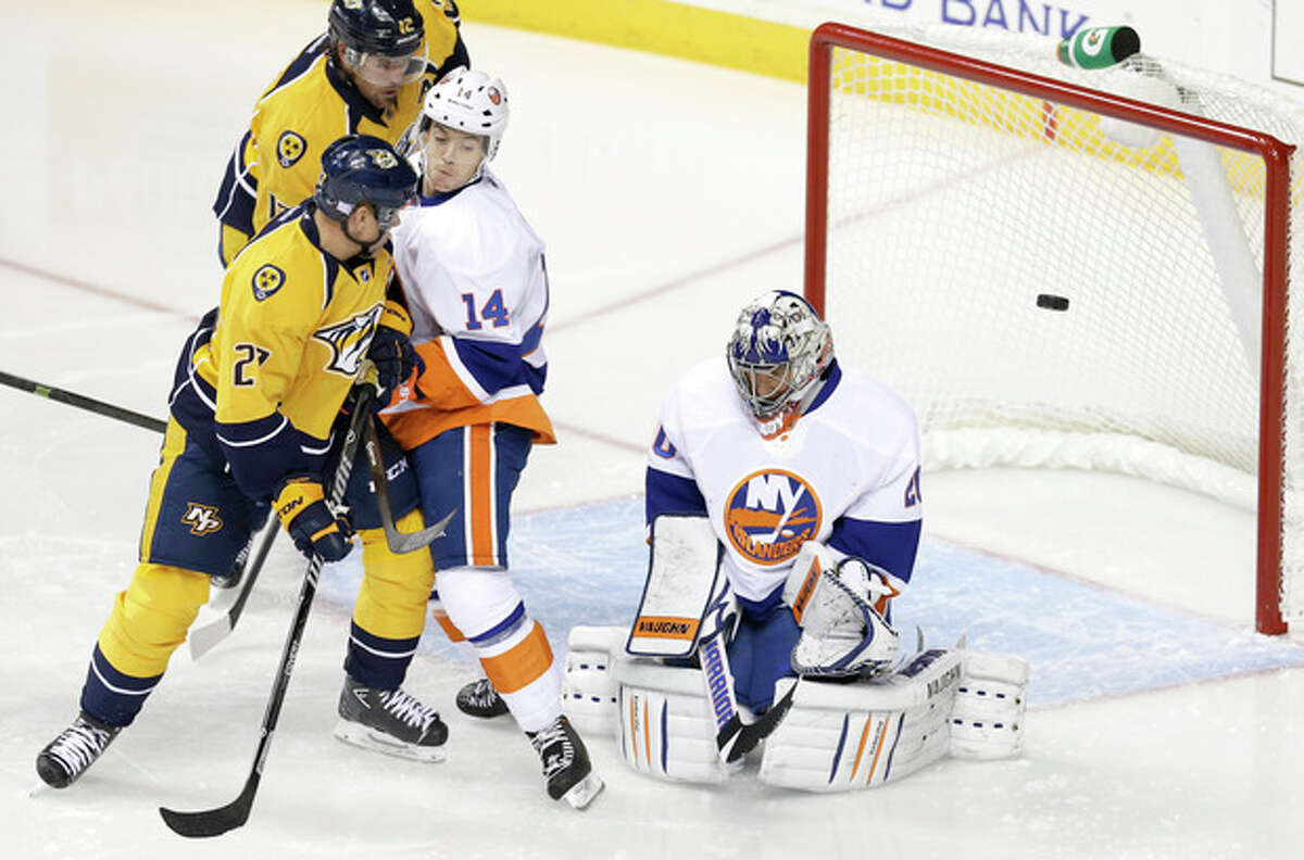 New York Islanders goalie Evgeni Nabokov, right, of Kazakhstan, blocks a shot as Thomas Hickey (14) and Nashville Predators forward Patric Hornqvist (27), of Sweden, battle in front of the net in the first period of an NHL hockey game on Saturday, Oct. 12, 2013, in Nashville, Tenn. (AP Photo/Mark Humphrey)