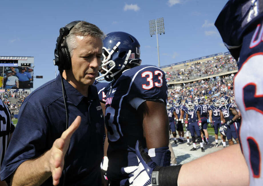 Connecticut's interim head coach T.J. Weist encourages players before an NCAA college football game against South Florida, in East Hartford, Conn., on Saturday, Oct. 12, 2013. (AP Photo/Fred Beckham)