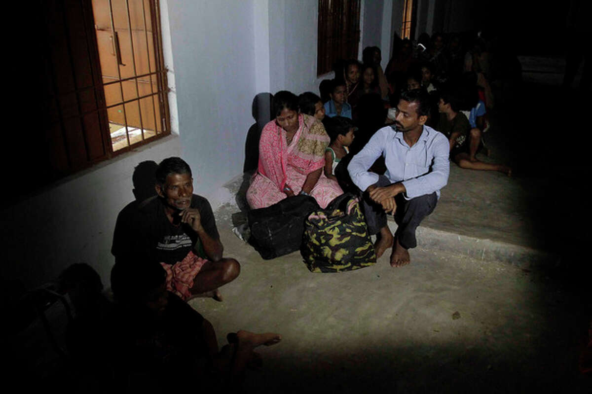Evacuated Indian villagers take shelter in a school building following a cyclone warning in Berhampur, India, Saturday, Oct. 12, 2013. Hundreds of thousands of people living along India's eastern coastline were taking shelter Saturday from a massive, powerful cyclone Phailin that was set to reach land packing destructive winds and heavy rains. (AP Photo/Bikas Das)