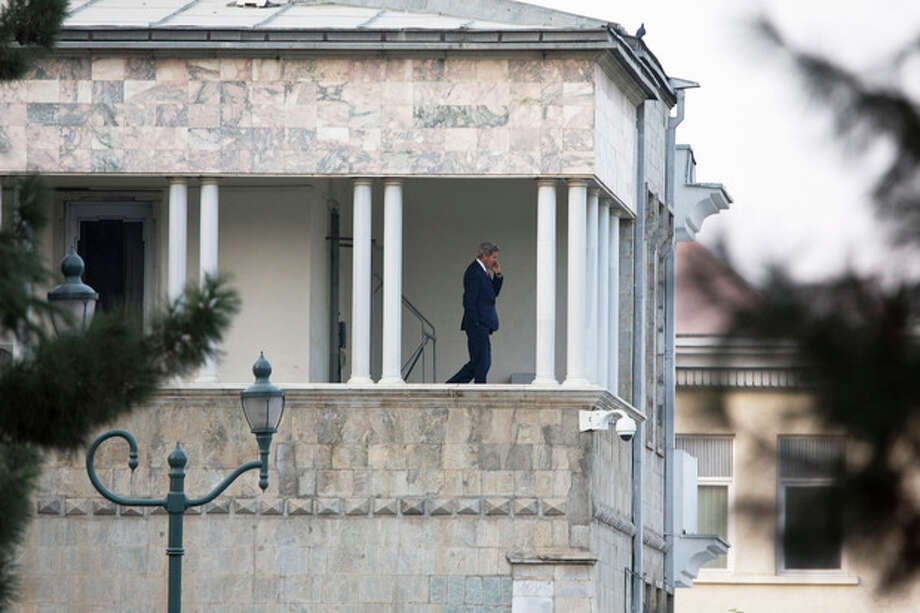 U.S. Secretary of State John Kerry paces while talking on his mobile phone from the second story of the Afghan Presidential Palace during a break in an extended meeting with Afghan President Hamid Karzai at the palace during an unannounced stop in Kabul, Afghanistan, on Saturday, Oct. 12, 2013, as a deadline approaches for a security deal about the future of U.S. troops in the country. (AP Photo/Jacquelyn Martin, Pool) / AP POOL
