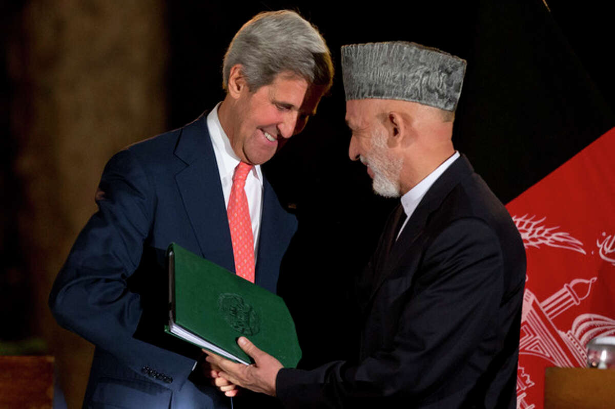 U.S. Secretary of State John Kerry, left, leans in toward Afghan President Hamid Karzai as they say goodbye at the end of a news conference announcing a tentative agreement between the two countries at the Presidential Palace during Kerry's unannounced stop in Kabul, Afghanistan, on Saturday, Oct. 12, 2013, as a deadline approaches for a security deal about the future of U.S. troops in the country. (AP Photo/Jacquelyn Martin, Pool)