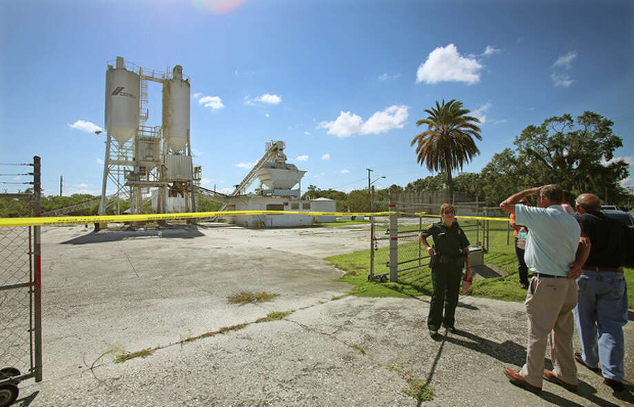 FILE - In this Sept. 10, 2013 file photo, Polk County Sheriff personnel investigate the death of 12-year-old girl, Rebecca Ann Sedwick, at an old cement plant in Lakeland, Fla. Two girls have been arrested in her death. Officials say she committed suicide after being bullied online for nearly a year. On Tuesday, Oct. 15, 2013 Polk County Sheriff Grady Judd will announce charges against the girls, age 12 and 14, in a press conference. (AP Photo/The Lakeland Ledger, Ernst Peters, File) / The Lakeland Ledger